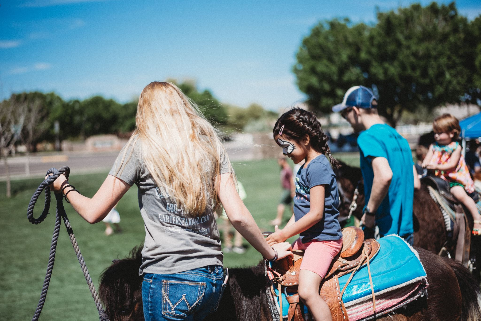 Assistant Walking Alongside a Brown Pony Rode by a Girl in Face Paint
