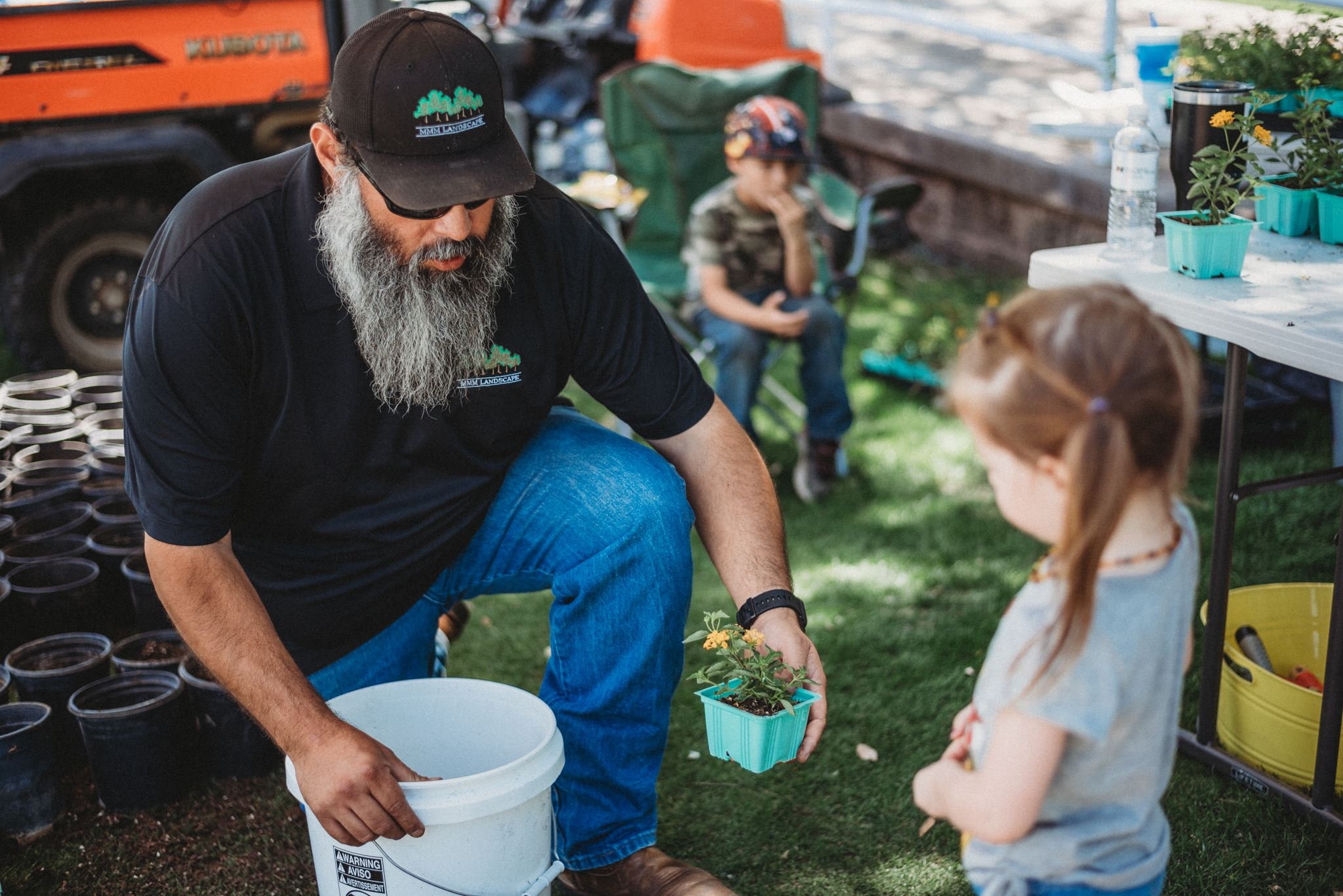 Bearded Man Ging a Young Girl a Potted Yellow Flower
