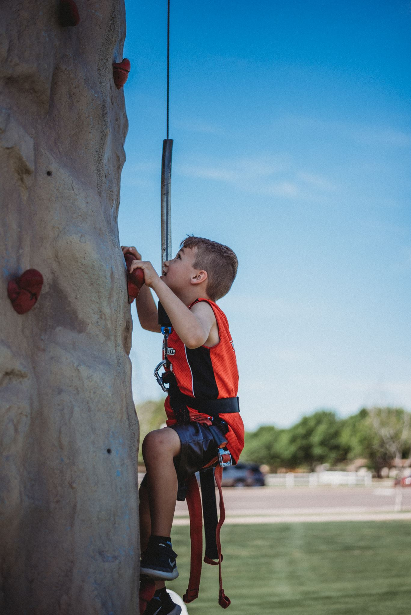 Boy Scaling a Rock Climbing Wall