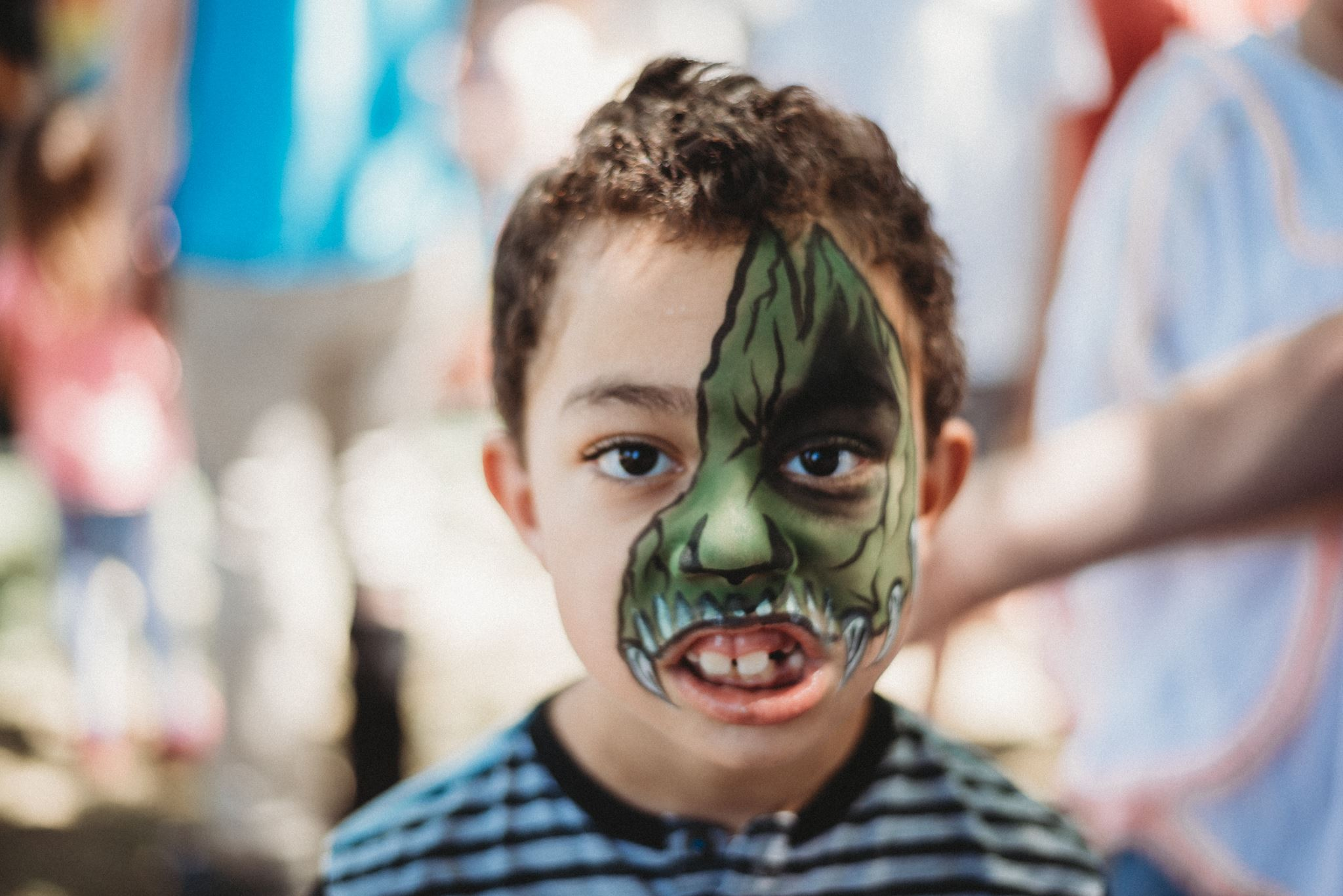 Boy with Dinosaur Face Paint Making a Scary Face for the Camera