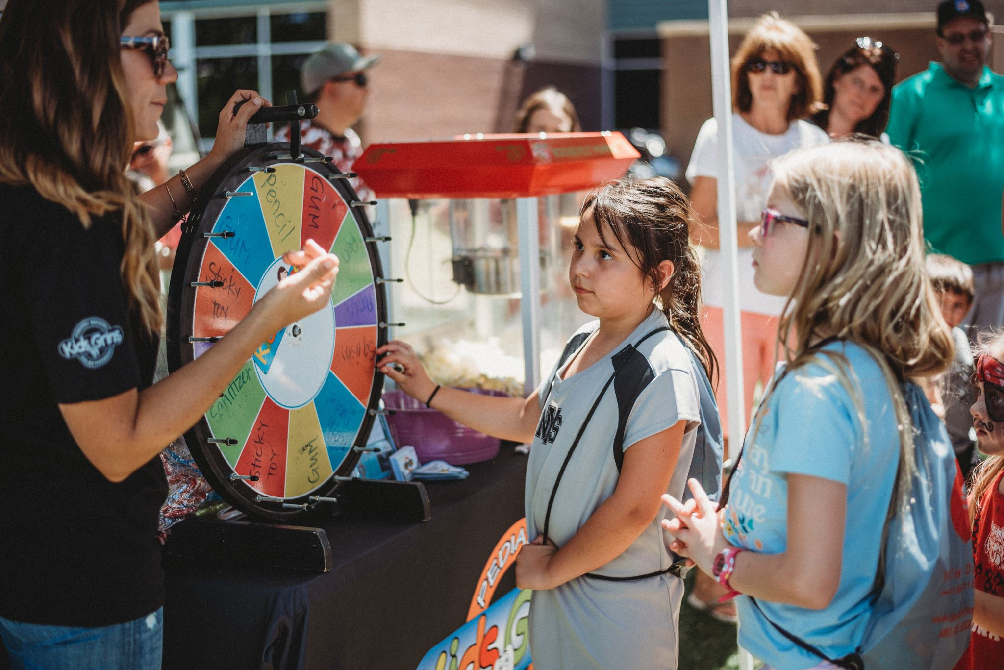 Children Talking to a Woman with a Prize Wheel