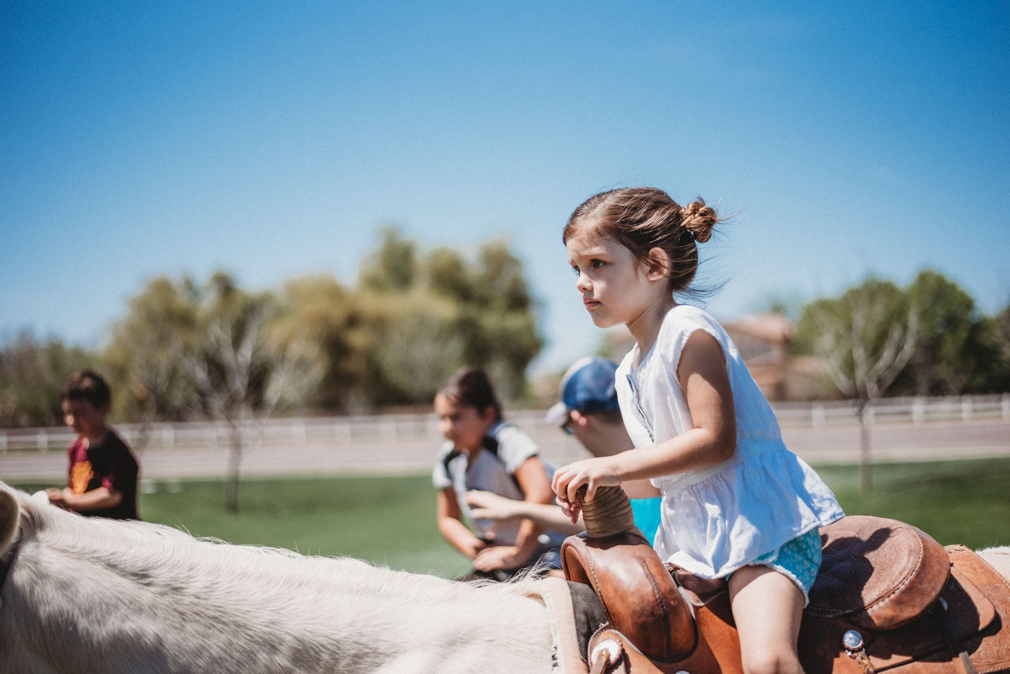 Young Girl Determinedly Riding a White Pony