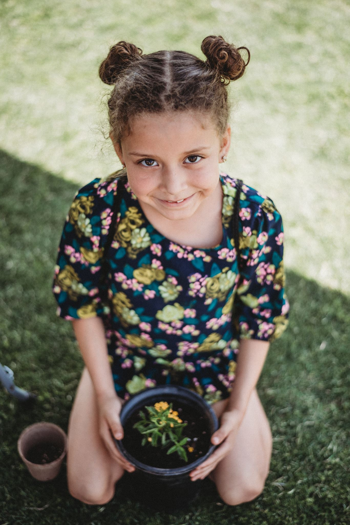 Young Girl Wearing a Floral Pattern Holding a Potted Flower