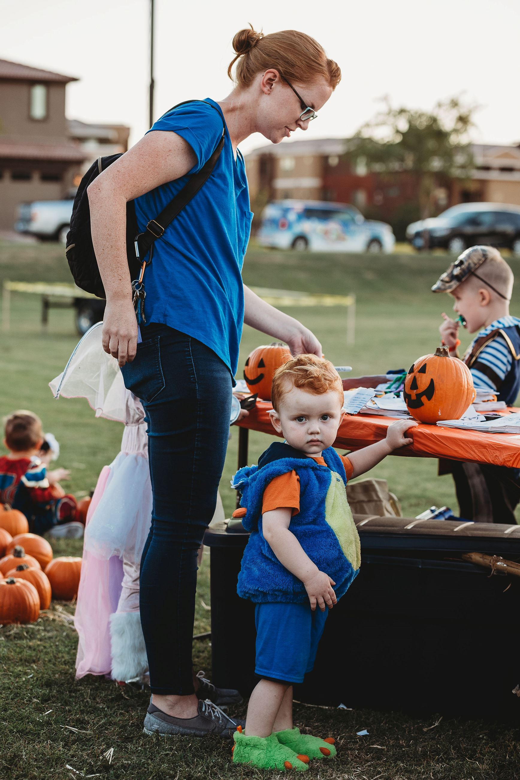 Toddler Carefully Watches the Camera While His Mother Finishes Painting a Face on a Pumpkin