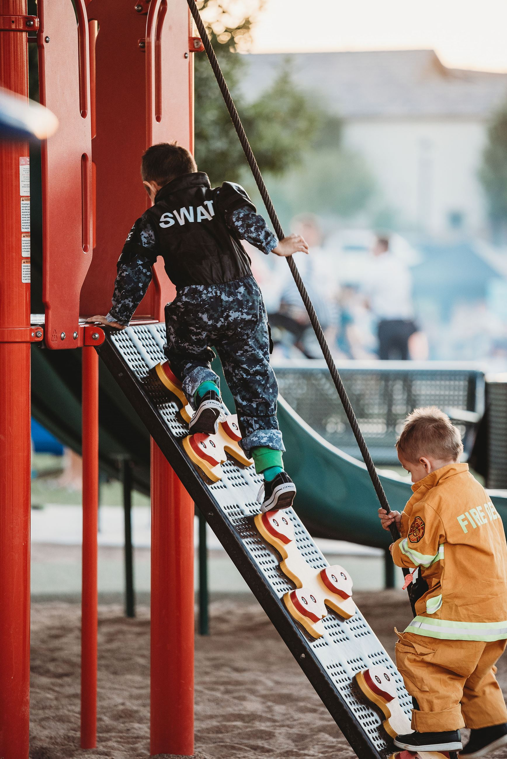 Two Young Boys Dressed as a SWAT Team Soldier and a Firefighter Climb a Play Structure