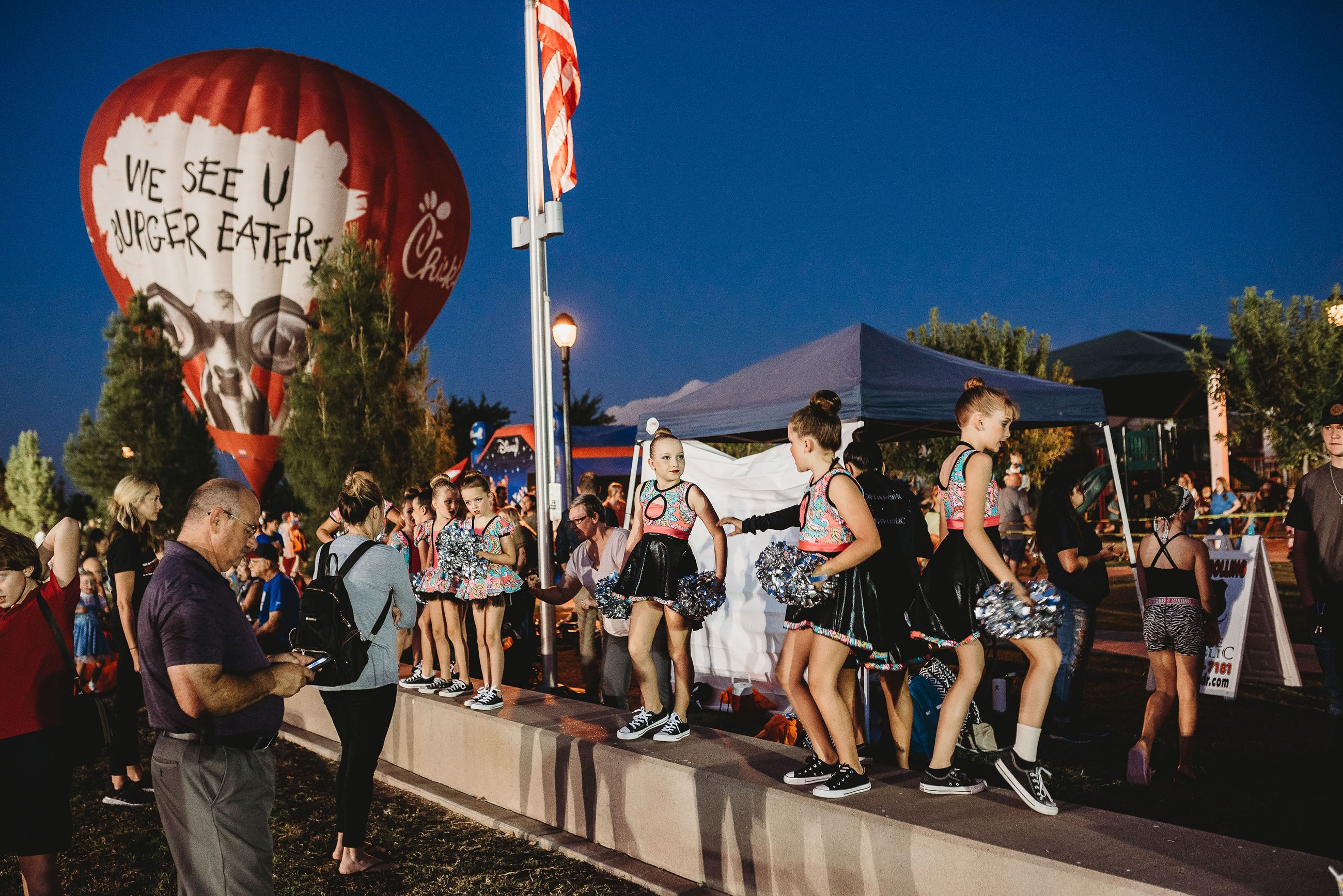 Young Cheerleaders Line up as the Festival Enters the Night -  a Big Chick-fil-A Hot Air Ballon Can