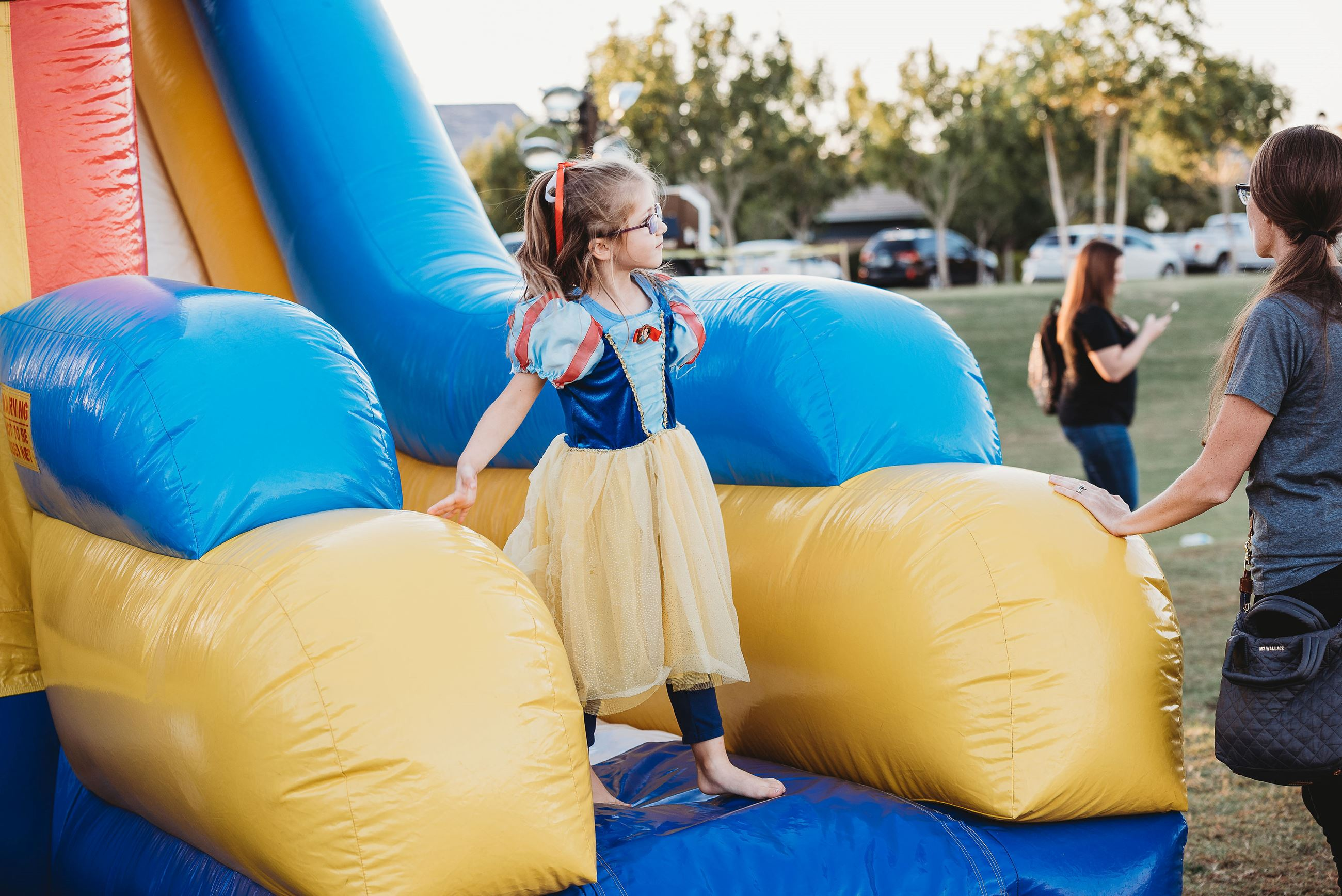 Young Girl Dressed as Snow White Standing at the Base of an Inflatable Slide