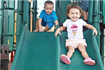 Two Children Slide down a Double Slide Together